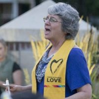 "Jonalu Johnstone, reverend at the Unitarian Universalist Fellowship, leads the group in song at the candlelight vigil in City Park on June 12, 2016. The group sang ""Singing for Our Lives"" by Holly Near and ""Stand"" by Amy Carol Webb. (George Walker 